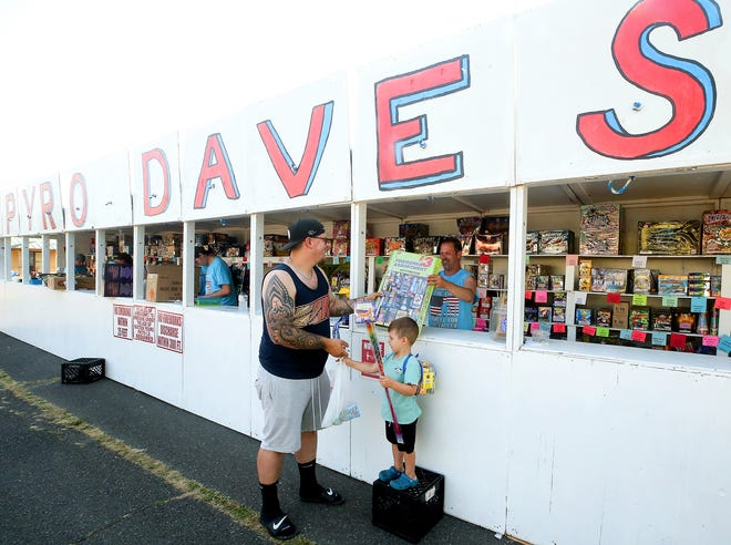 Employee Jason Goetz, right, hands purchases to Skyler Mullins from behind the counter after helping Mullins and his son Liam, 3, pick out fireworks at Pyro Dave's Fireworks Stand in Bremerton on Tuesday. Fire officials are urging extreme caution for those using personal fireworks on the Fourth of July, as the region recovers from a stretch of record-breaking high temperatures.
