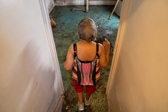 """Marsha Stewart, 73, walks to the basement of her house on June 29, 2021, on Marlborough Street in Detroit that was damaged by flooding. Stewart, who has lived in the house since 1986 says she hasn't seen anything like this. """"I hyperventilate when I think about all the damage,"""" she said from her basement."""