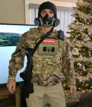 """Steven Thurlow  is seen in this photo wearing a gas mask, armed with a knife and what appears to be an AR-15 style rifle. He also is wearing tactical gear with a """"Boogaloo"""" patch."""