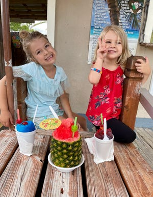 Avery and Marie Guidry enjoy a frozen treat on a hot summer day thanks to ISIS SnowBalls in Crowley Thursday, June 29, 2021.