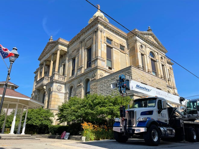 Lee Restoration LTD brings in a large crane to move materials to the top of the Marion County Courthouse for improvements to its roof, tower and Lady of Justice.