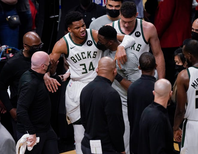 Milwaukee Bucks' Giannis Antetokounmpo is helped off the court after he and Atlanta Hawks' Clint Capela fell during the second half of Game 4 of the Eastern Conference finals on Tuesday. Antetokounmpo didn't play Game 5 with a hyperextended left knee and has again been ruled out for Game 6.