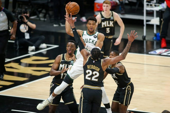 Milwaukee Bucks forward Giannis Antetokounmpo (34) passes over Atlanta Hawks forward Cam Reddish (22) in the first quarter during game four of the Eastern Conference Finals.