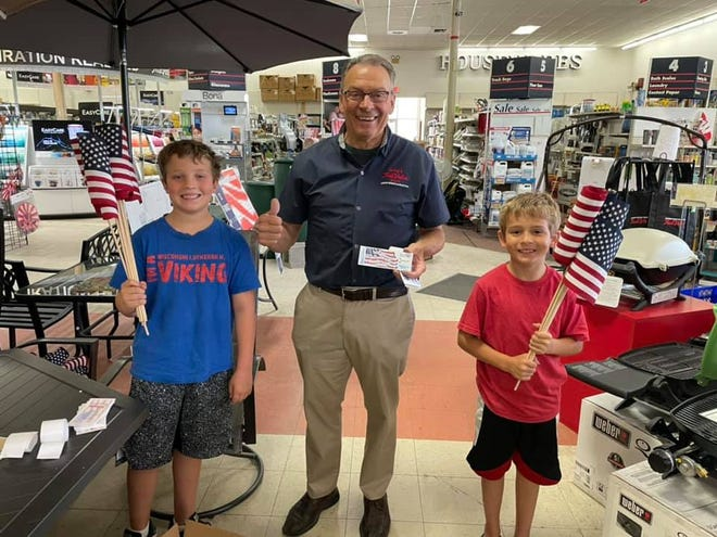 For the last 19 years Greg's True Value has filled St. Francis with flags for the Fourth of July. Here, Leo Frank, 11, Greg Schlecht (owner), and Landen Frank, 9, hold some of the flags that will be distributed.