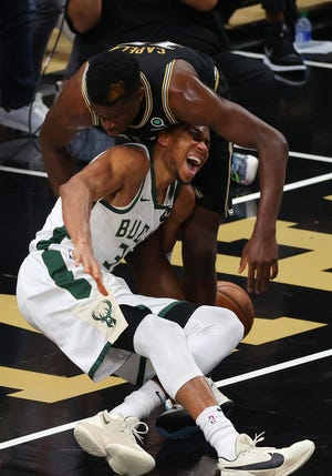 Giannis Antetokounmpo of the Milwaukee Bucks is injured during a play against Atlanta's Clint Capela during the second half of Game Four of the Eastern Conference finals Tuedsay at State Farm Arena on June 29, 2021 in Atlanta, Georgia.