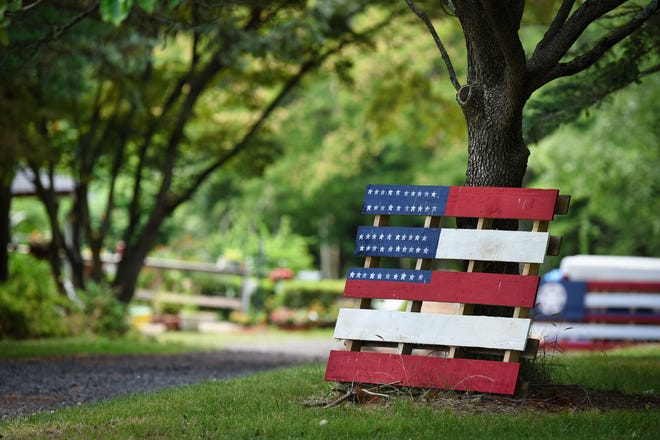 Photo of a wood pallet painted into an American flag leans against a tree. Susan Davieau Patti of Montville painted and displayed it outside of her home, on 06/30/21.