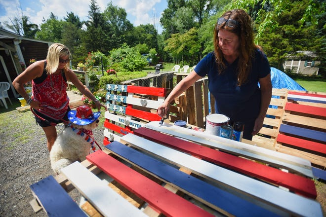 Jodi Beyer of Montville paints a wood pallet into an American flag on June 30, 2021.