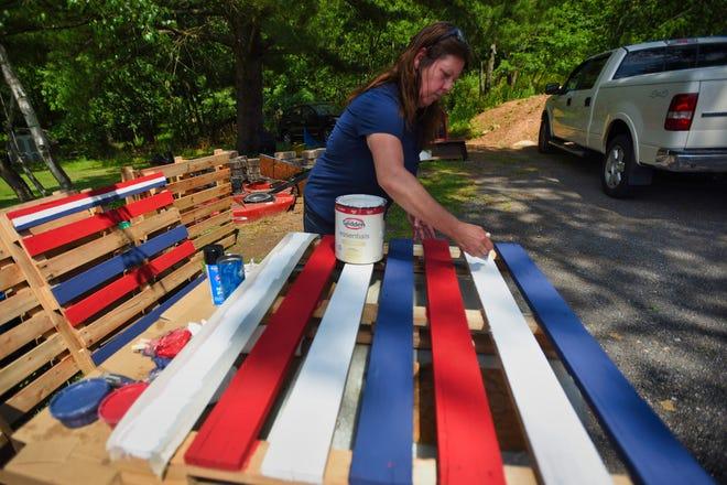Susan Davieau Patti paints a wood pallet to display around Montville on June 30, 2021.