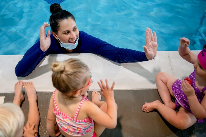 Instructor Maya Brannan high fives student Eleanor Bates, 2, during their class at SafeSplash Cool Springs in Franklin, Tenn, on Wednesday, June 30, 2021.