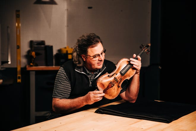 Vince Gill examines Country Music Hall of Fame member Roy Acuff's fiddle. Gill acquired Acuff's fiddle and donated it to the museum's permanent collection.