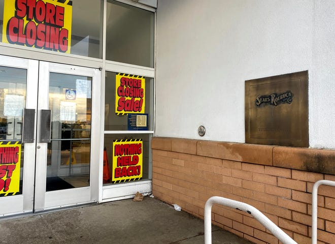 """Signs indicating the Sears at Westland Shopping Center is closing. A panel that says """"Sears Roebuck and Co."""" is on the wall near the doors."""