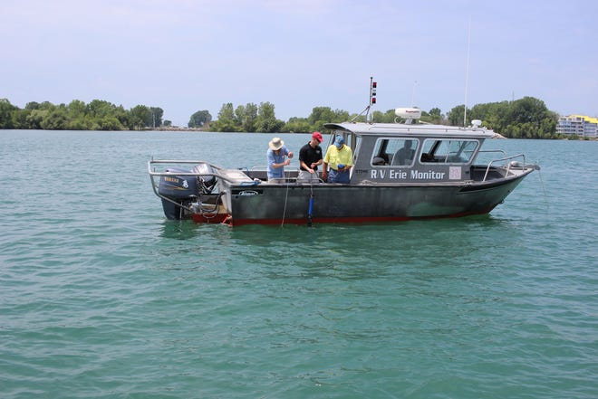 Scientists aboard a research vessel from Ohio State University's Stone Lab on Gibraltar Island take measurements in Lake Erie as part of ongoing studies of harmful algal blooms.