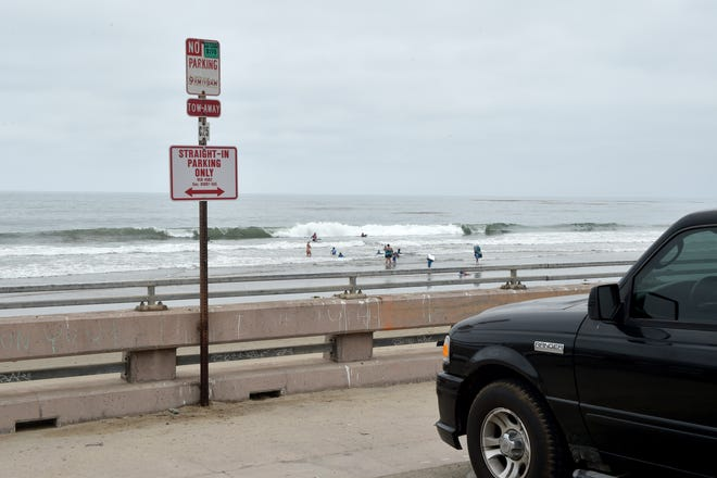 A sign warns visitors of a new pilot parking program that started in late June for the Rincon Parkway. All vehicles must park straight-in and not parallel along a sea-wall near to Solimar Beach. More spaces have been allotted for the program.