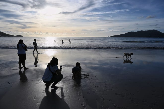 People walk along Patong Beach in Phuket, Thailand, days before the Phuket Sandbox tourism program opens the island up to vaccinated tourists beginning on July 1, 2021.