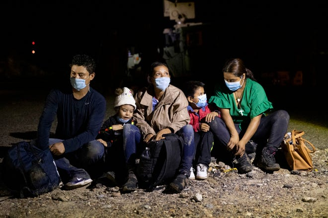 A group of immigrants from Central America wait to be processed by a Border Patrol agent June 30 after they crossed the Rio Grande in a raft from Ciudad Miguel Alemán, Tamaulipas, Mexico, to Roma, Texas.