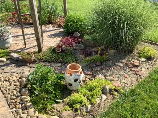 This backyard friendship garden has been divided into sections, including a rock garden showcasing a variety of sedums and a beautiful stand of morning light grass accented by garden pottery.