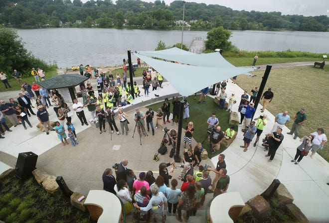 Summit Metro Parks Executive Director Lisa King and board Chairman Herb Newman, bottom center, use oversize scissors to cut the ribbon at Summit Lake Nature Center's grand opening Thursday.