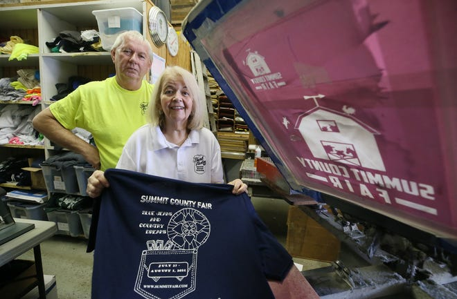 Kathy and Ron Scheetz, owners of the Akron Shirt Factory in Norton, show a T-shirt made for the Summit County Fair's directors.