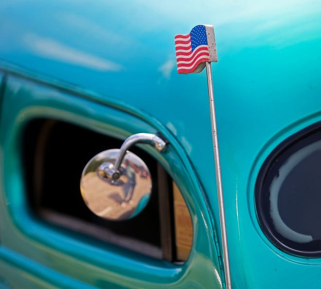 An American flag antenna topper is displayed on a classic car.