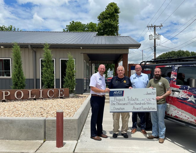 Arvest Bank commercial banker Chad Cox and Arvest Bank loan manager David Nickel presented the check to Project Tribute executive director Jon Beckloff and Dewey Police Chief Mike Shea.