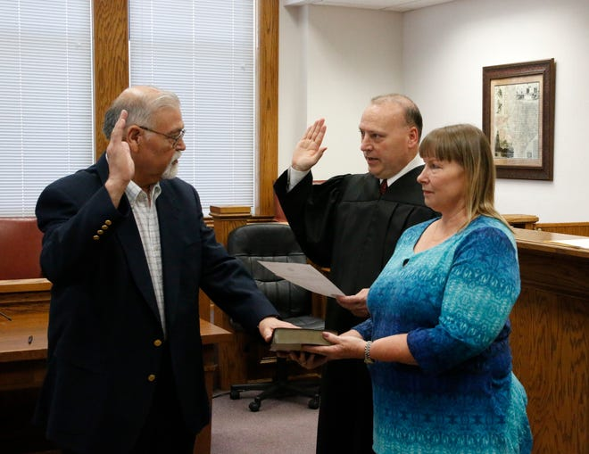 Ted Perez places his hand on a Bible held by his wife, Charlene, as Brown County Judge Paul Lilly swears Perez in as Precinct 4 justice of the peace Wednesday in the Brown County Courtroom.