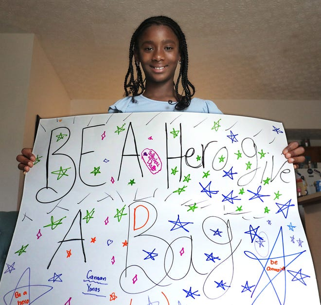 Pickerington middle school student Safiatou Diallo, 10, founded an organization called Greater Purpose Africa to collect school supplies for children in Guinea, West Africa. She is holding a sign she made to spread the word about her project.