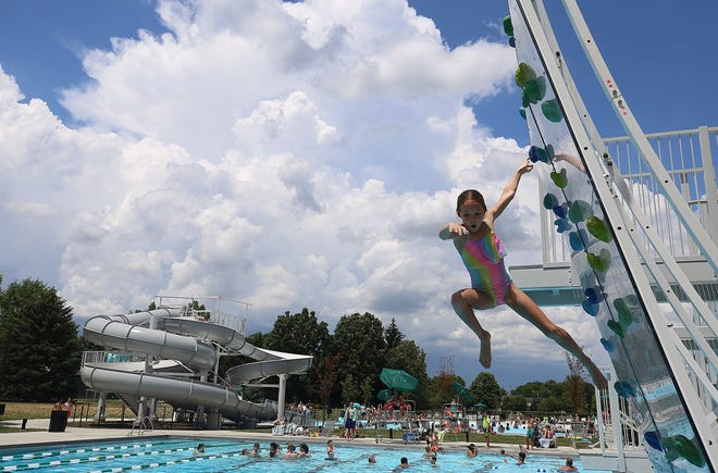 Ella Reel, 8, leaps from the climbing wall at the Dublin Community Pool North on June 29.