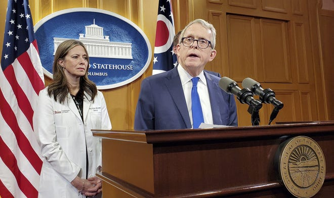 Gov. Mike DeWine is joined by then-Ohio Health Director Dr. Amy Acton during a March 9 news conference.