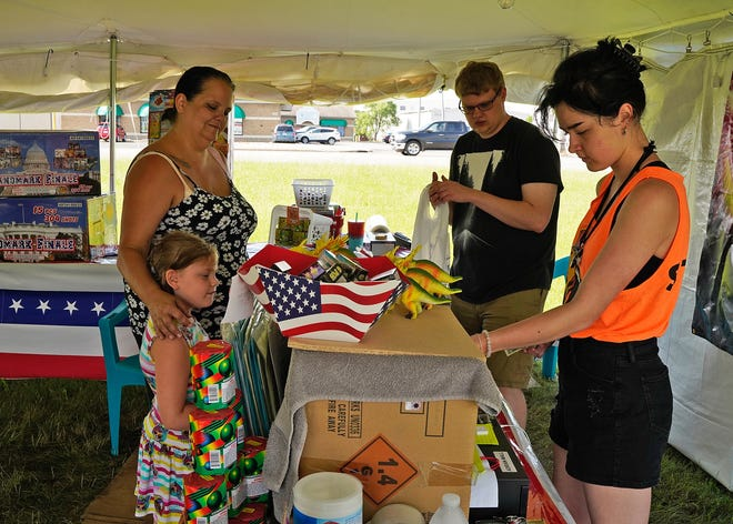 Debra Loynes and daughter Nevaeh, 6, of Adrian purchase fireworks from Shay McCarthy of Tipton and Conner Fawcett of Blissfield Thursday at a fireworks tent on U.S. 223 in Adrian.