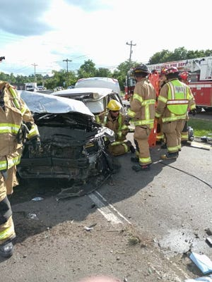 Columbia Fire & Rescue Captain Monty Bland, kneeling center, leads a team of responders following a motor vehicle extrication at the scene of a vehicle collision at the intersection of Nashville Highway and Carters Creek Pike in Columbia, Tenn., on Wednesday, June 30, 2021.