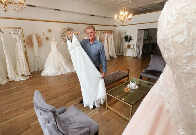 Joe Hearn holds up one of the wedding dresses at downtown DeLand's District Bridal, set to open at the end of the month. Hearn, a longtime event planner, said weddings are picking back up as people continue to get vaccinated against COVID-19, which caused many couples last year to postpone their nuptials.