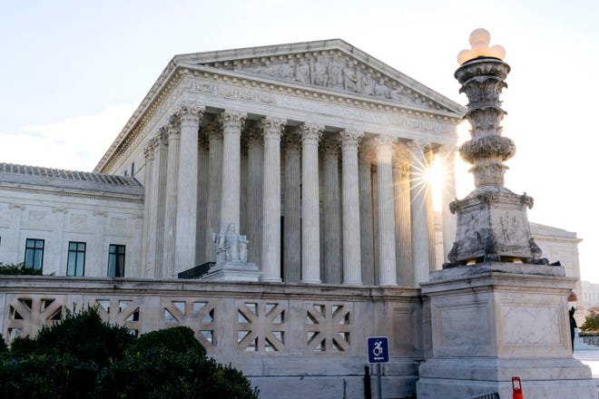 In this Nov. 10, 2020, file photo the sun rises behind the U.S. Supreme Court in Washington.