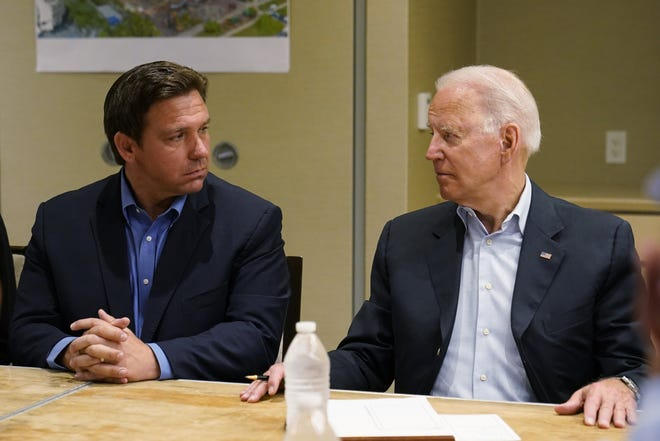 President Joe Biden, right, looks at Florida Gov. Ron DeSantis during a briefing with first responders and local officials in Miami on Thursday on the condo tower that collapsed in Surfside last week.