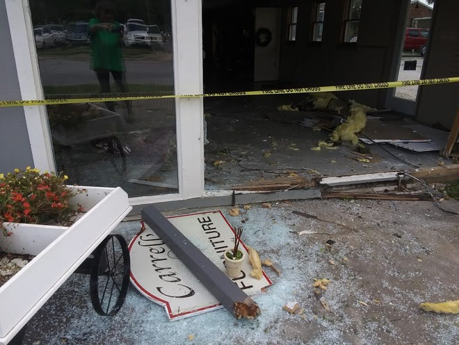 Shattered glass litters the ground outside Carrell's Furniture store in Ellettsville Wednesday.