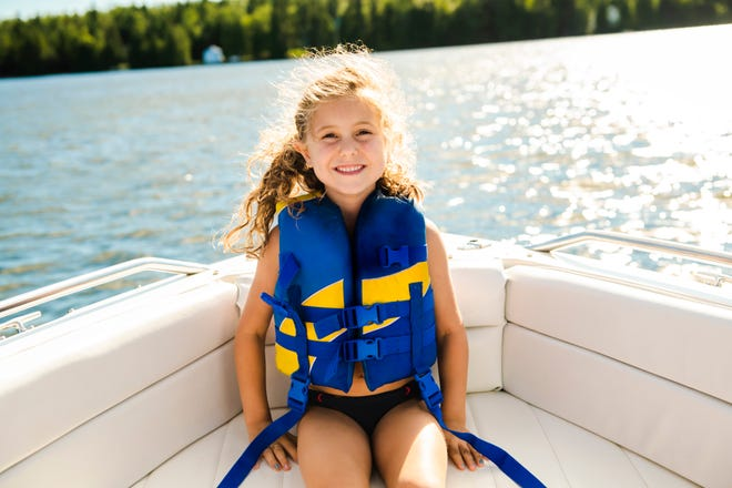 A child with safety vest on the lake boat.