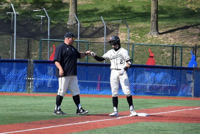 Shown is Lansing baseball head coach Michael Basler fist bumping his son, Peyton, during a 2021 contest. Peyton was an all-state honorable mention selection and United Kansas Conference first team selection at shortstop.