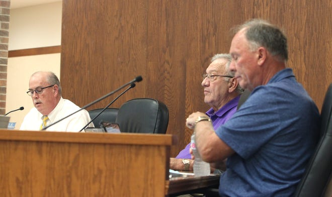 Moberly Mayor Jerry Jeffrey, left, and councilmen John Kimmons and Cole Davis, right, listen to a report shared while they participate in a city council business meeting held at City Hall.