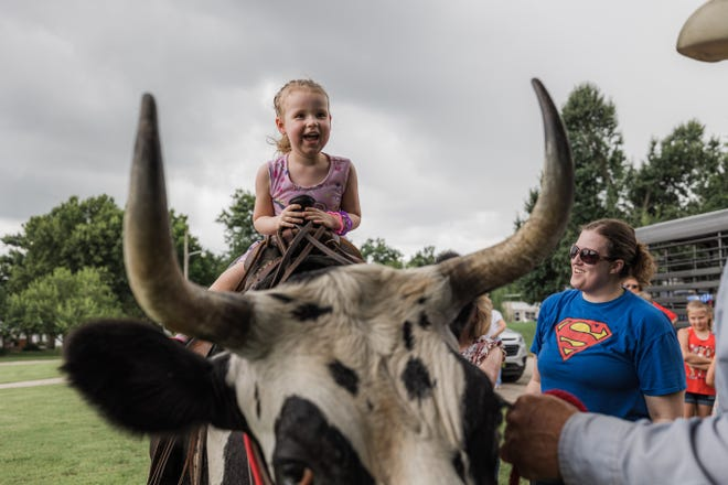 Ashley Turney watches her daughter, Clara-Mae, giggle with excitement as she takes her turn riding longhorn steer Micky Jr. outside the Pawhuska Public Library on Wednesday, June 30. The steer rides were an element of the Summer Reading Program for 2021 at the library. Summer Reading began May 26 and continued each Wednesday in June.
