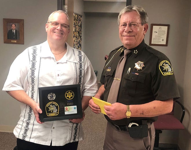 Emmet County Sheriff Pete Wallin (right) congratulates sheriff's deputy Brad George, who retired Wednesday following 21 years of service to Emmet County citizens.