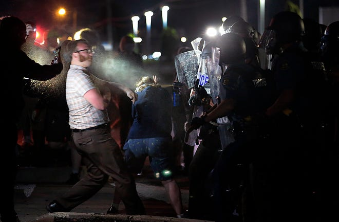 """FILE - In this June 21, 2020 file photo, protesters are hit with a chemical spray from police officers outside police headquarters in Florissant, Mo. A Missouri bill awaiting the signature of Gov. Mike Parson includes a so-called police """"bill of rights"""" that establishes guidelines for investigating officers accused of wrongdoing. Critics say it reduces police accountability at a time when many states are enacting laws to make police more accountable. (Robert Cohen/St. Louis Post-Dispatch via AP)"""