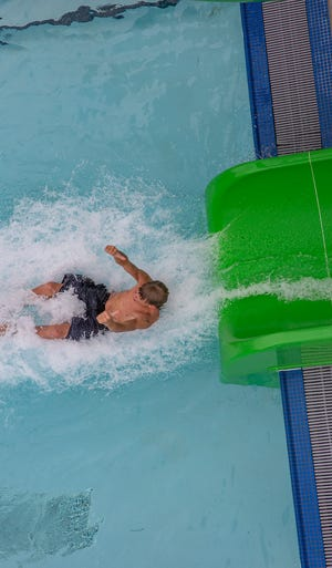 Ryder Mialkovsky splashes into the pool as he leaves the water slide at Echo Hollow Pool. Triple digit temperatures are expected Friday and officials are encouraging people to keep cool in places such as alibrary, community center or shopping center, or a park with plenty of shade or a water feature, like a splash pad.