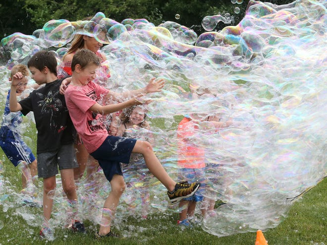 """Children brace for a surge of bubbles during Freedom Fest at Boettler Park in Green on Saturday, June 26, 2021. Gary Pearlman, better known at """"Dr. U.R. Awesome,"""" provided the bubbles for the event."""