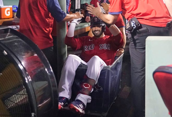 Boston Red Sox's J.D. Martinez celebrates his three-run home run with a ride in a laundry cart during the Red Sox's win against the Kansas City Royals at Fenway Park.