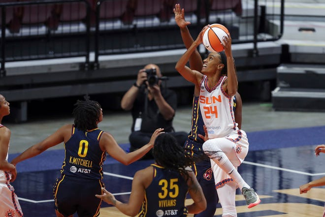 Connecticut Sun's DeWanna Bonner (24) shoots over Indiana Fever's Kelsey Mitchell (0) and Victoria Vivians (35) during a game in Uncasville.