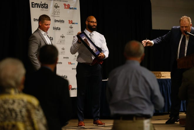 Michael Wilhoite is presented with a plaque signifying being accepted into the Shawnee County Sports Hall of Fame at Wednesday's Shawnee County Sports awards and hall of fame ceremony at the Capitol Plaza Hotel.