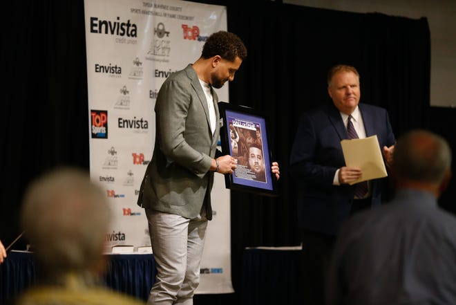 Kyle Weems is presented with a plaque signifiying being accepted into the Shawnee County Sports Hall of Fame at Wednesday's Shawnee County Sports awards and hall of fame ceremony at the Capitol Plaza Hotel.