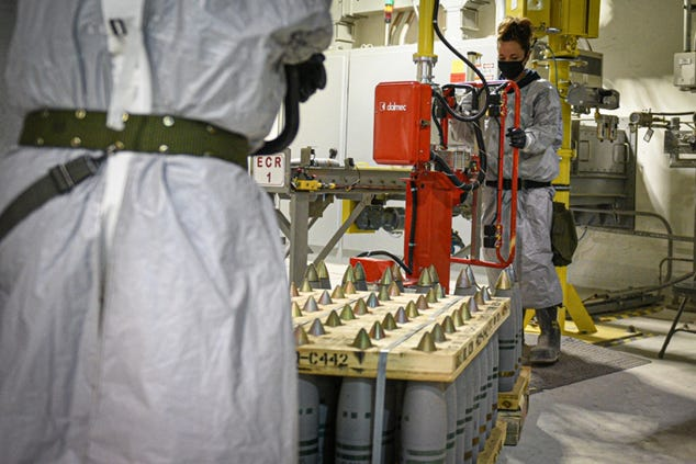 A Pueblo Chemical Agent-Destruction Pilot Plant ordnance technician uses a lift assist to transfer a 105mm projectile onto a conveyor in February 2021.