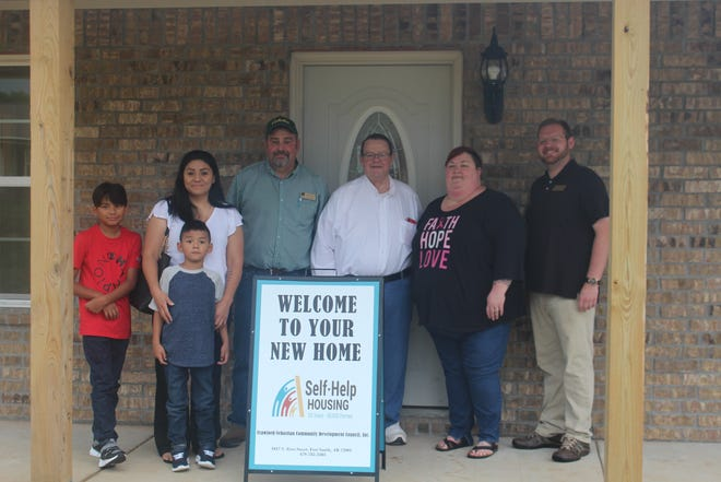 The staff of the Homeownership & Asset Development Center at Crawford-Sebastian Community Development Council welcome Lizeth Solis and her two sons to their new home in Cedarville.