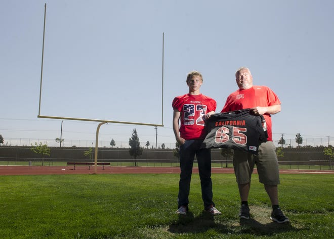 Robert Metzger, right, holds up a jersey he wore in the Down Under Bowl in Australia while standing next to his son Noah in 2016. Metzger has been announced as Oak Hills' head coach, taking over for Robert Kistner, who recently stepped down from the program.