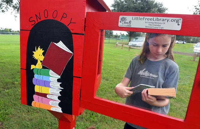 Autumn Neilson-Herring and her 11-year-old daughter Nellie, who is pictured looking at books, recently visited the Little Free Library their family set up next to one of the playgrounds at Chain of Lakes Park in Titusville.